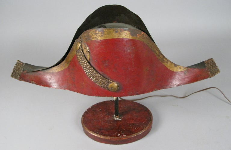 A very charming early 20th century lamp in the form of a tole metal Napoleonic chapeau, mounted on a wood base. Wired to accept a small bulb with a standard base. It is really more of a lighted object than a light source.