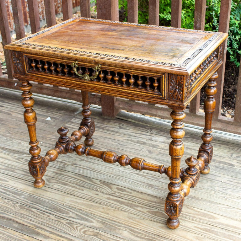 This charming writing desk features a unique design with spindle front drawer and spindle detail at the sides, turned legs, and ornate brass pull on the drawer. The drawer on this desk spans the entire width and offers plenty of interior storage.