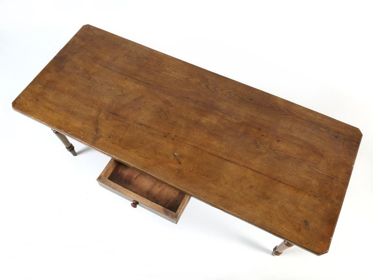 Antique country French oak farm table, with a unique pass-through drawer. This particular antique country French farm table was probably made between 1890 and 1920. Our in-house restoration department, thoroughly went through the table from the