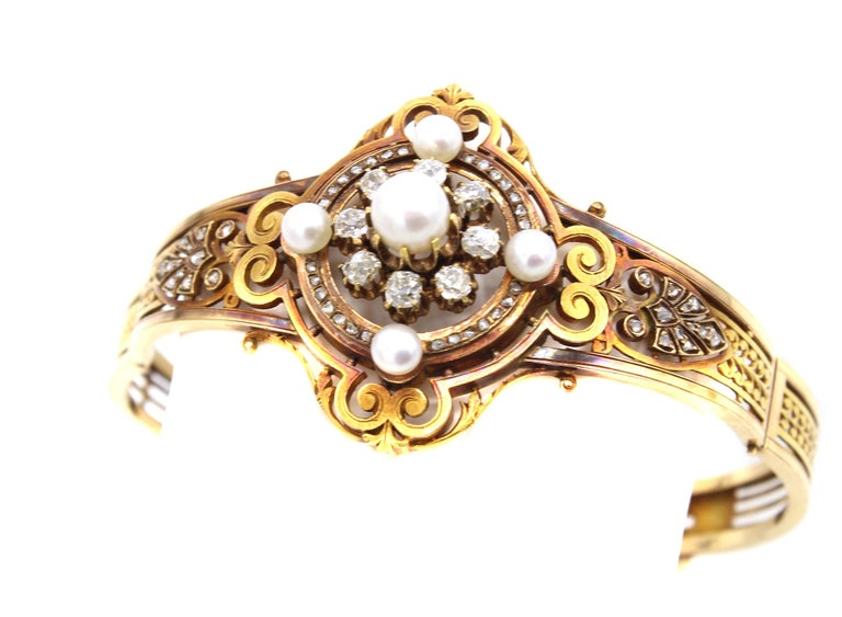 Amazingly well designed and hand-crafted this mid-19th century French bangle bracelet exhibits wonderful azur work in 18 Karat gold. The central element is embellished by one larger and 4 smaller white lustrous pearls and the center pearl is