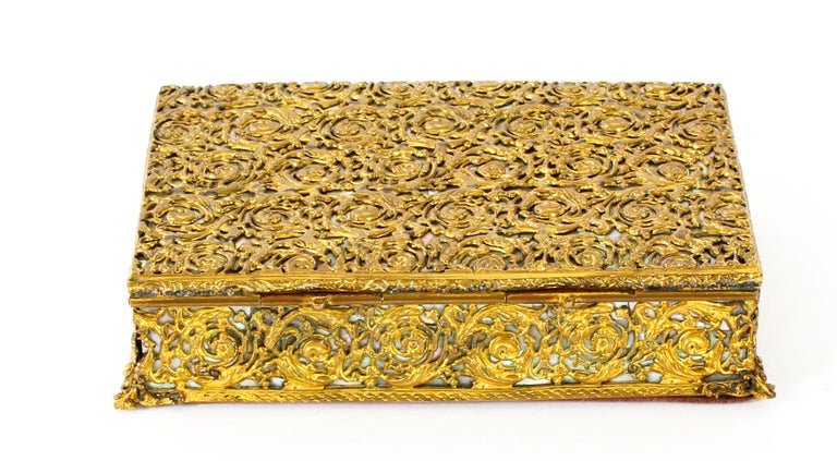 This is a beautiful antique gilded ormolu and mother of pearl casket, circa 1870 in date.   The top, front, sides and back feature beautifully cast ormolu decorative trellis work over of a mother of pearl ground.   The interior is lined with the