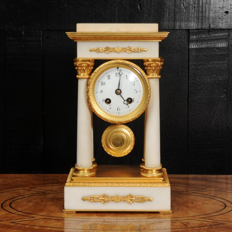 A beautiful small antique French portico clock retailed by the famous Maple & Co of London, circa 1890. Very well made in white marble and ormolu (finely gilded doré bronze). Neoclassical in design, four delicate Corinthian columns support the top