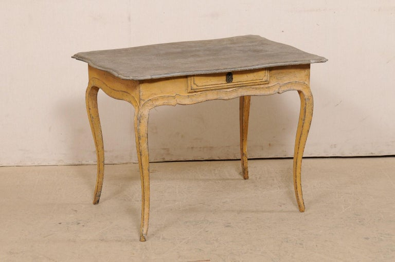 A French smaller-sized painted wood table, with single drawer, from the turn of the 18th and 19th century. This antique table from France features a rectangular-shaped top with lovely scalloped edging, which overhangs the scalloped apron that houses