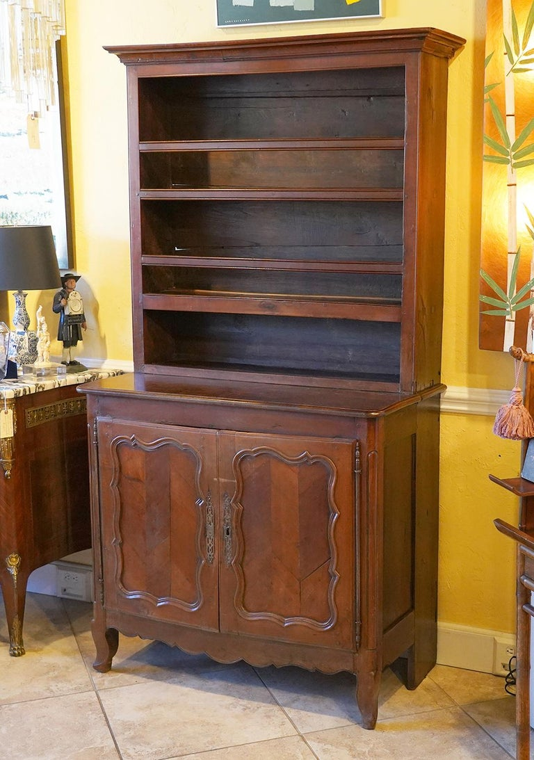 This antique French Provincial fruitwood buffet features an upper part with fixed shelves adorned by a molded cornice resting on a deeper lower cabinet part with Rococo style parquetry paneled doors opening up to a one shelf interior. The buffet
