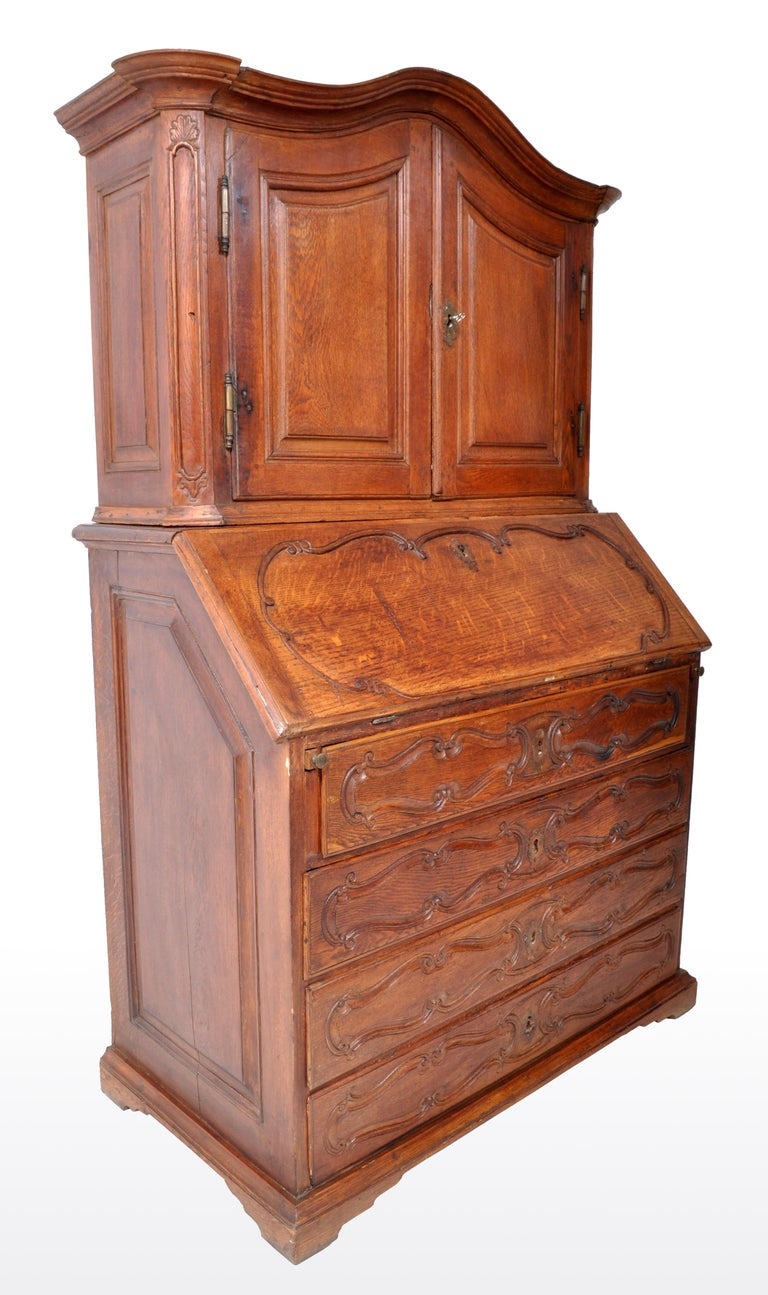 Antique French Provincial oak secretary/bureau bookcase, circa 1770. The two section desk, having an arched top with twin fielded paneled cupboard doors below enclosing a single shelf. The base having a fall front writing surface enclosing a fitted