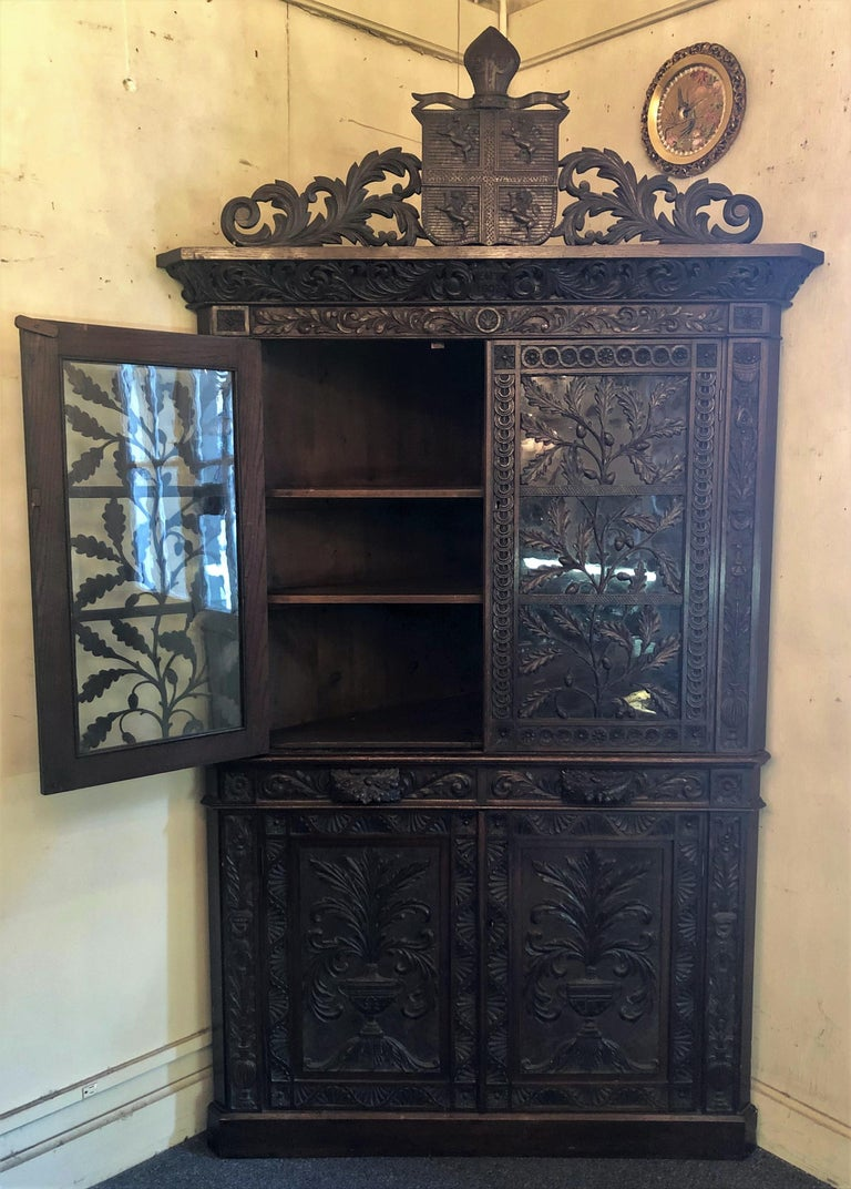 Magnificent antique French Provincial ornately carved oak corner cabinet with heraldic crest and rampant lions.