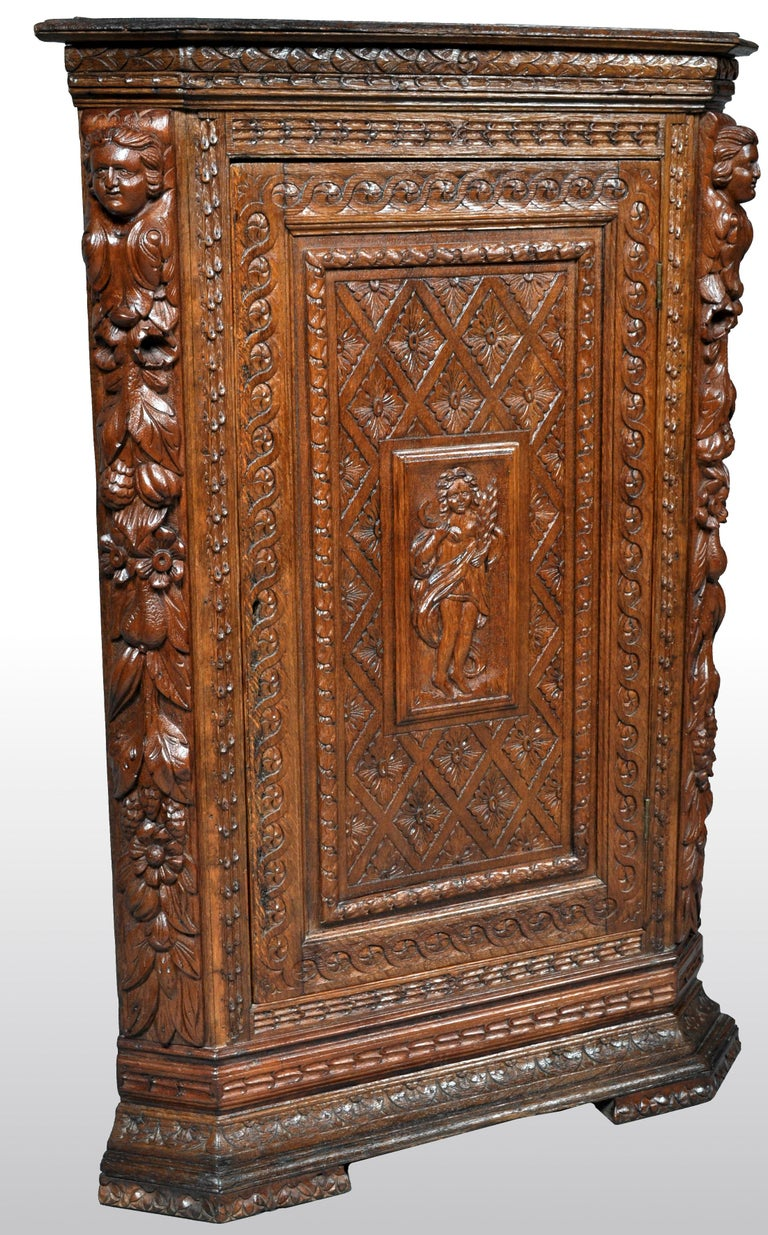 Antique French baroque carved oak corner cabinet, circa 1780. The top of the cabinet having a low gallery and below highly carved figural and fruiting garland pilasters to either side. The cabinet having a single door with bands of intertwined