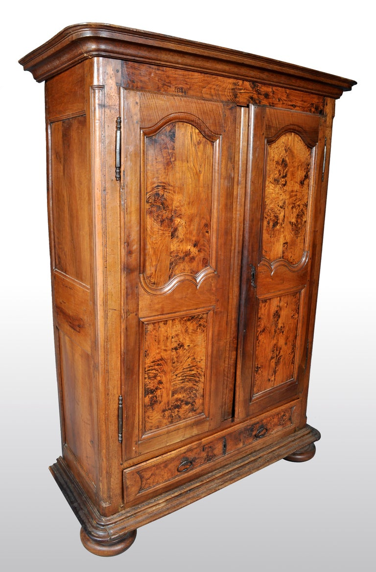 Antique French Provincial finely figured walnut wedding armoire, circa 1750. The armoire having a removable stepped cornice with a pair of shaped fielded panel doors below, having the original iron hinges and lock. To the base is a single drawer,