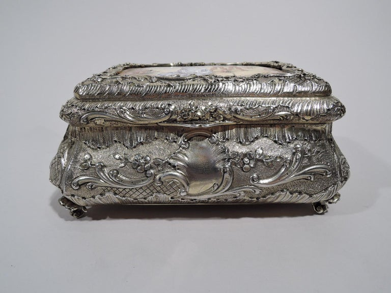 French gilt 950 silver casket, circa 1900. Bombe with chased scrolls and flowers on granulated and diaper ground. On front, asymmetrical cartouche (vacant). Four scrolled corner supports. Cover hinged and raised and inset with enamel plaque