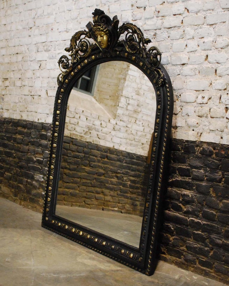 An antique French mirror made in the ancient European Renaissance style.  The frame has a gadrooned edge and pearl beading surrounding the glass. The arched top is decorated with a central positioned serene women's head flanked by elegant
