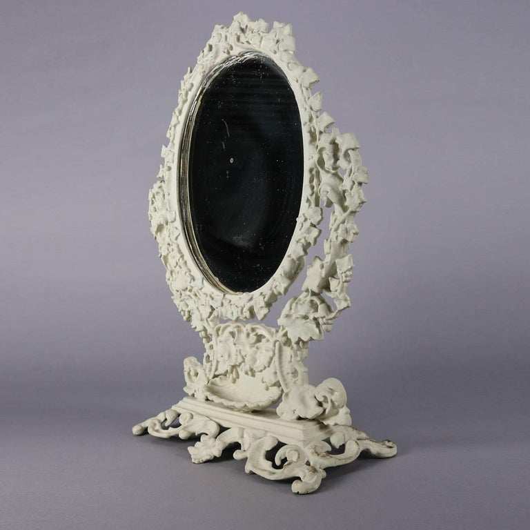An antique French Rococo tabletop cast iron dressing mirror features oval form with white painted cast grape and leaf frame with lower shell form ring tray on pierced scroll form footed base, circa 1890.  Measures: 20