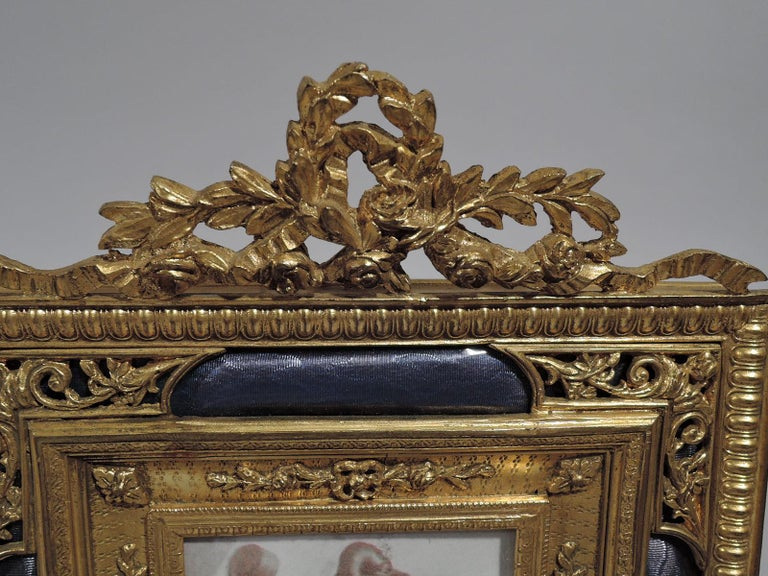 Turn-of-the-century French gilt bronze picture frame with lilac enamel. Rectangular window in concave surround with applied garlands in turn surround by wraparound tubular lilac enamel covered with pierced ornament at corners. Beaded, imbricated