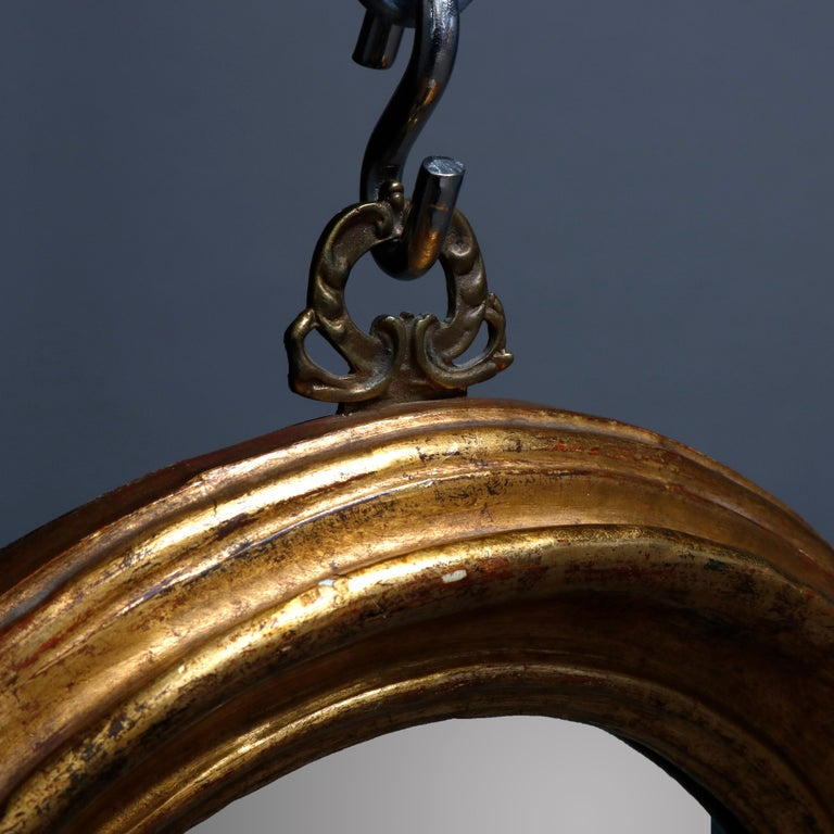An antique French Rococo wall mirror offers giltwood frame in stylized shield form, circa 1920  ***DELIVERY NOTICE – Due to COVID-19 we have employed LIMITED-TO-NO-CONTACT PRACTICES in the transfer of purchased items. Additionally, for those who