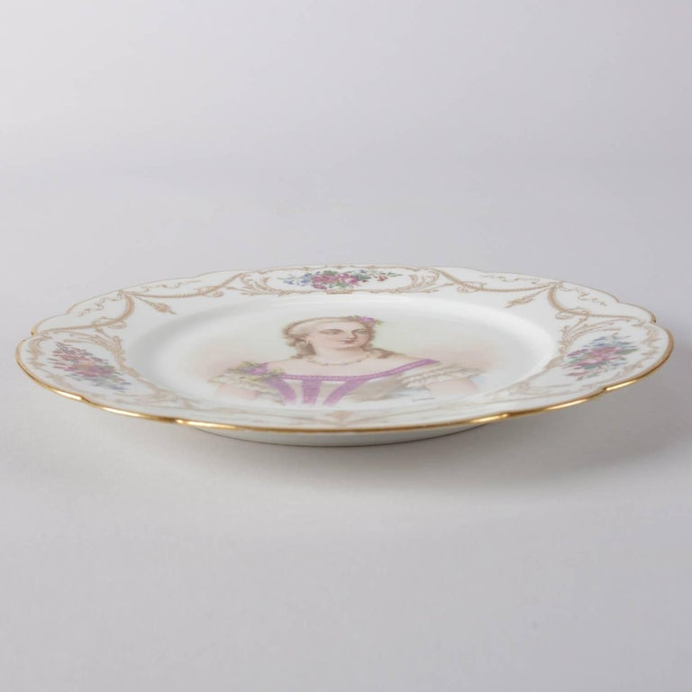 Antique French Sevres porcelain hand-painted porcelain portrait plate features central portrait signed lower right Debrise, scalloped border with floral reserves and gilt garland and scroll accents, en verso with Sevres stamp,