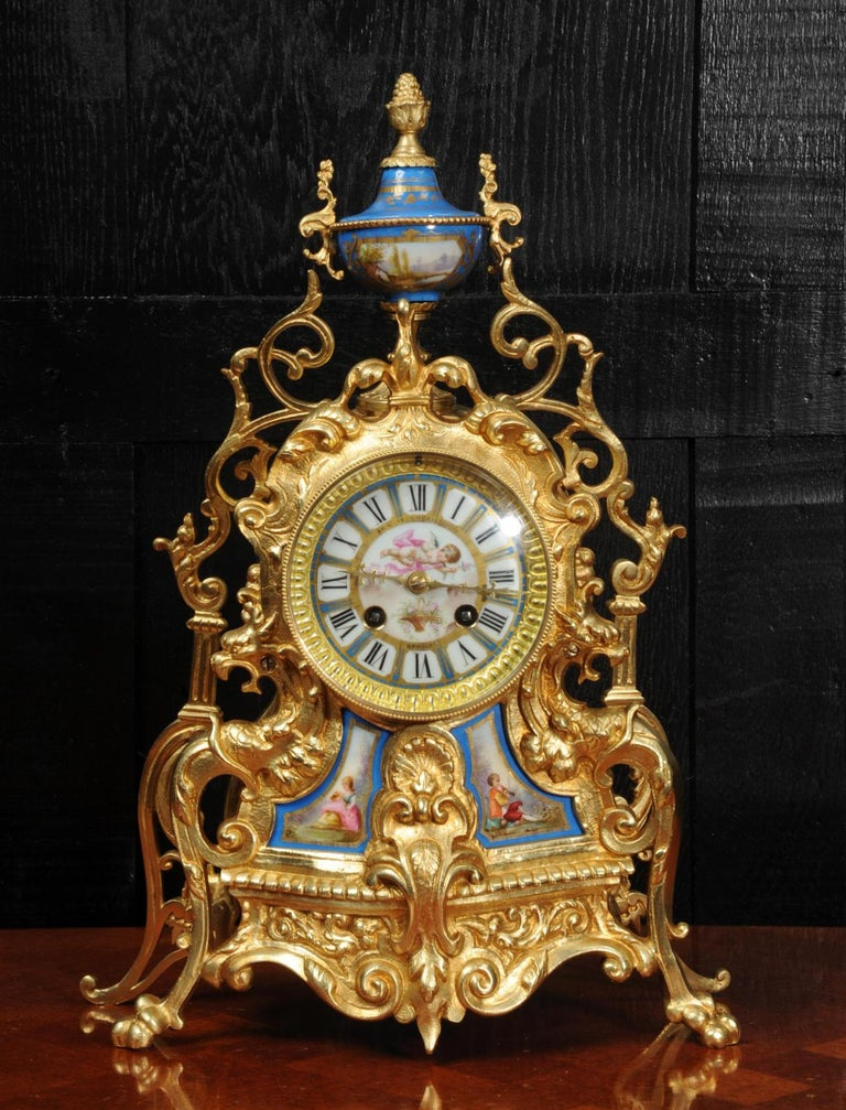A beautiful antique French gilt bronze clock with exquisitely decorated Sèrves style porcelain panels, urn and dial. It is Baroque in style with scrolling foliage and mythical creatures and dates from around 1870. The pair of panels show a charming