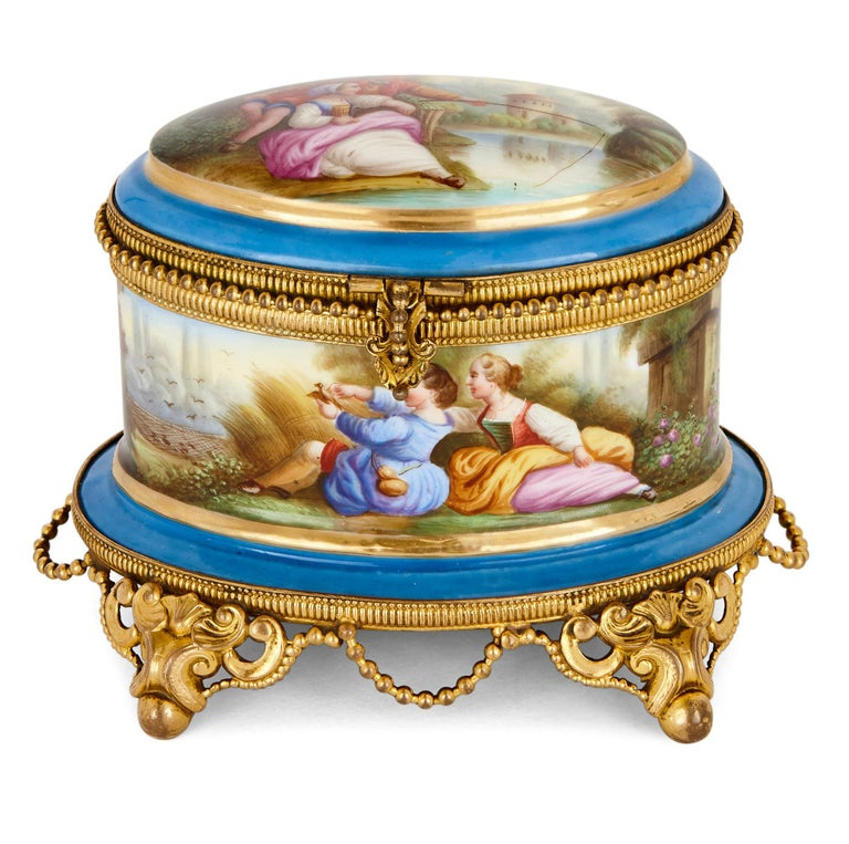 Of elliptical shape, this Sevres style porcelain perfume box contains fitted space for two glass perfume bottles. These bottles, which are mounted with gilt metal on their lids and around their necks, feature painted miniature scenes executed in