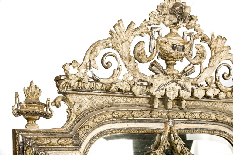 An impressive and rich decorated Louis XVI mirror that was made in Northern France in 1905.  The mirror frame was made of solid pine, has a segment arched top, and was decorated with cast ornaments. The ornate crest features many classical elements