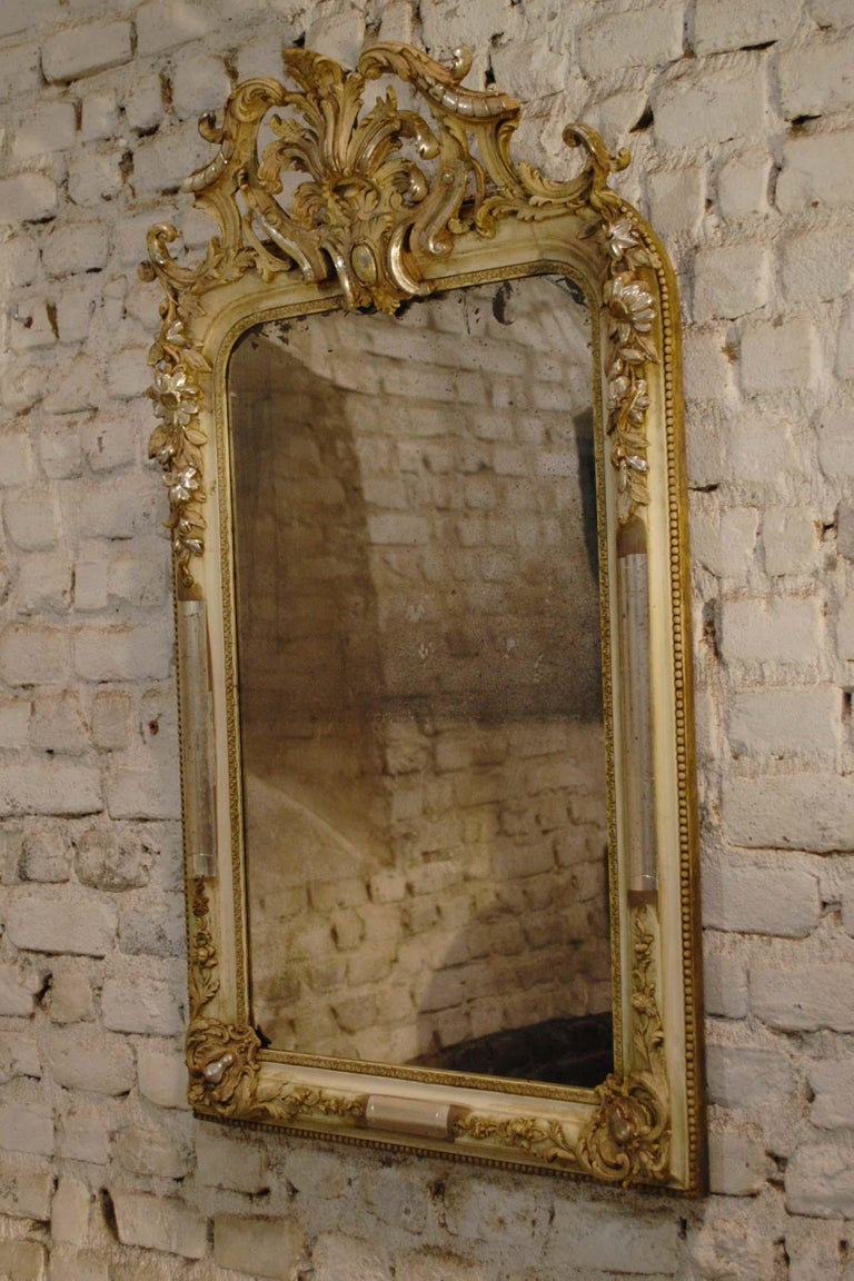 This beautiful mirror is partially silver leaf gilded and shows the bone color of the gesso. The frame has the upper rounded corners typical for the Louis Philippe style. It features rich ornaments around the frame, such as bay leaf, scallops,