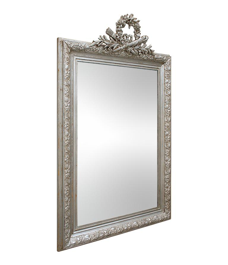 Antique silver mirror with a pediment, quiver, torch and arrows, Louis XVI style knot and foliage and flowers. Antique frame Louis Philippe style decorated with pearls and flowers. Re-gilding to the patinated silvered leaf. Modern glass mirror.