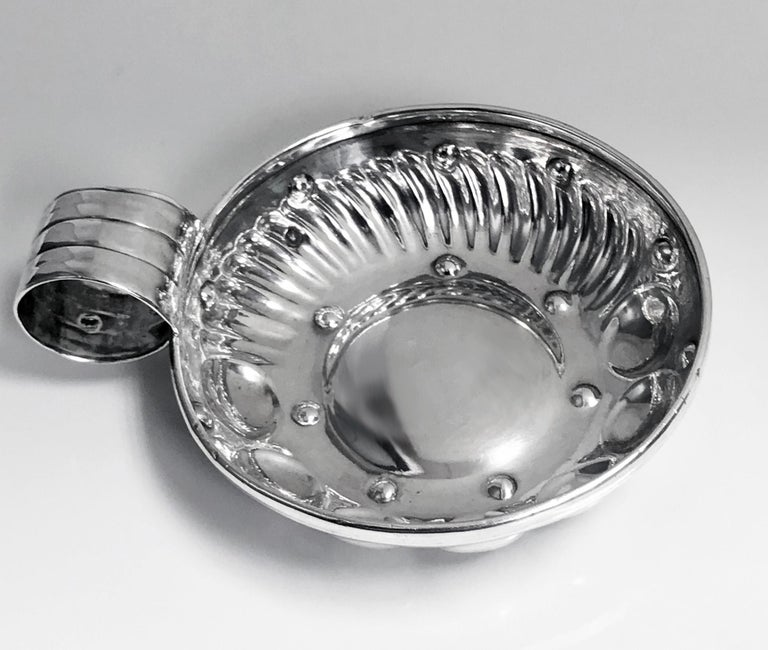 Antique French silver tastevin circa 1880, CT for Cesar Tonnelier, Minerva head 1st std. The test de vin of usual form, the lower part of bowl with a surround of concave and swirl lobate style decoration, ribbed thumb piece handle. Marked on handle