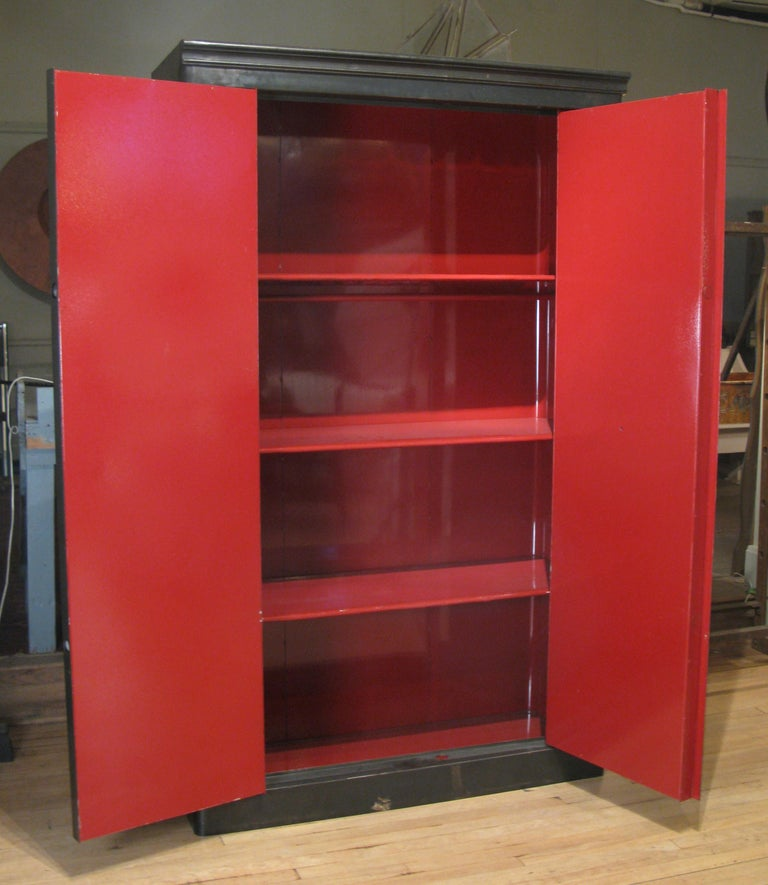 A remarkable antique 1940s French steel locking safe cabinet, restored with a lacquered Chinese red interior. The cabinet has 3 removable shelves, and a hanging rod as well. With its original key and dial locking mechanism.