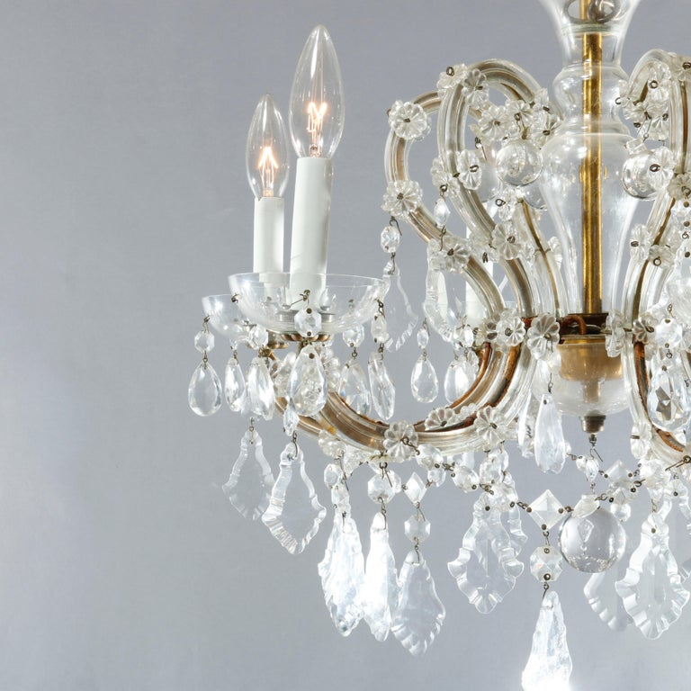 An antique French style chandelier offers brass frame with six scroll form arms terminating in candle lights, strung and cut crystals throughout, c1930  Measures: 37.5