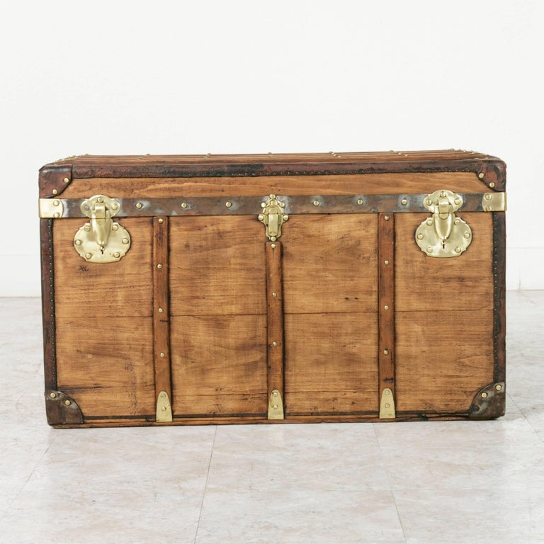 This French beechwood steam trunk from the turn of the 20th century features wooden runners detailed with brass rivets and its original brass locks. Its leather trim and corners offered protection from damage when traveling, and its original leather