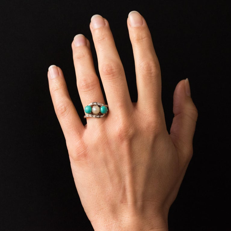 Ring in 18 carat yellow gold, horse head hallmark.  This ring features a claw set a natural pearl accentuated by round turquoise cabochons on each side all set within curves of rose cut diamonds.  Length: 1.8 cm, width 1.2 cm, thickness of the ring