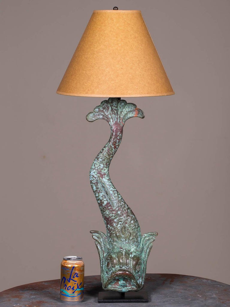 A marvelous antique French copper dolphin waterspout custom lamp from a wall fountain circa 1895 retaining its original finish now mounted on a custom iron stand and topped with a bronzed paper shade. Please notice the sensuous curve of the dolphin