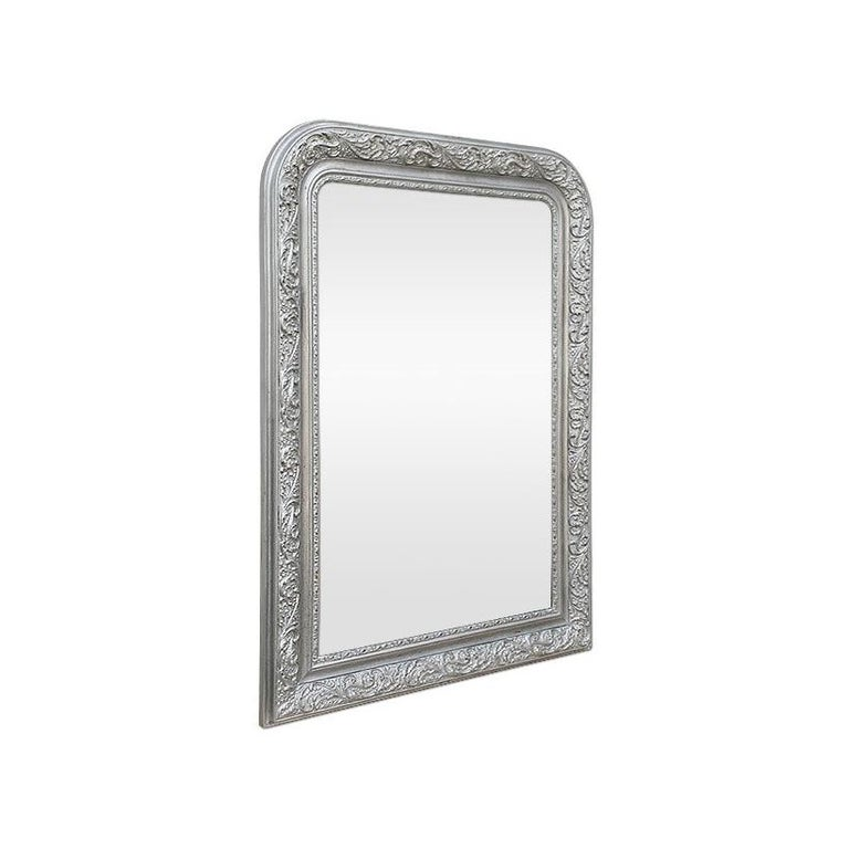 Antique french wall mirror, Louis-Philippe style. Re-gilding to the patinated silvered leaf, decoration of the antique frame with leafs and small flowers. Modern glass mirror. Antique frame width: 10.5 cm.