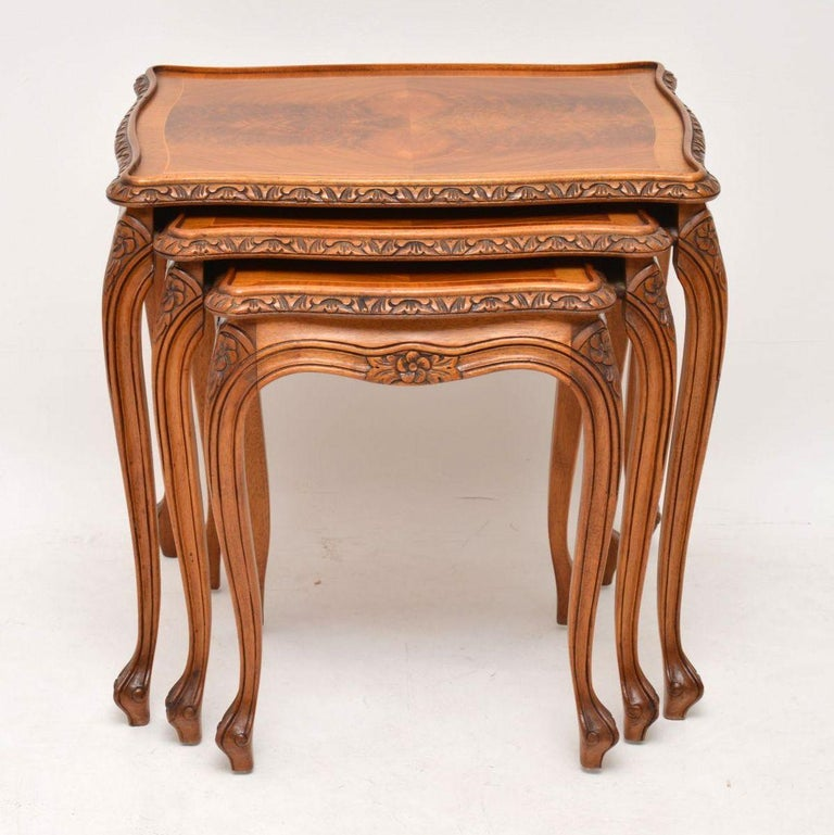 Antique French style walnut nest of three tables in excellent condition and dating to circa 1930s period. They are of high quality and have fine carvings around the shaped tops, between and on the tops of the solid walnut cabriole legs. The table