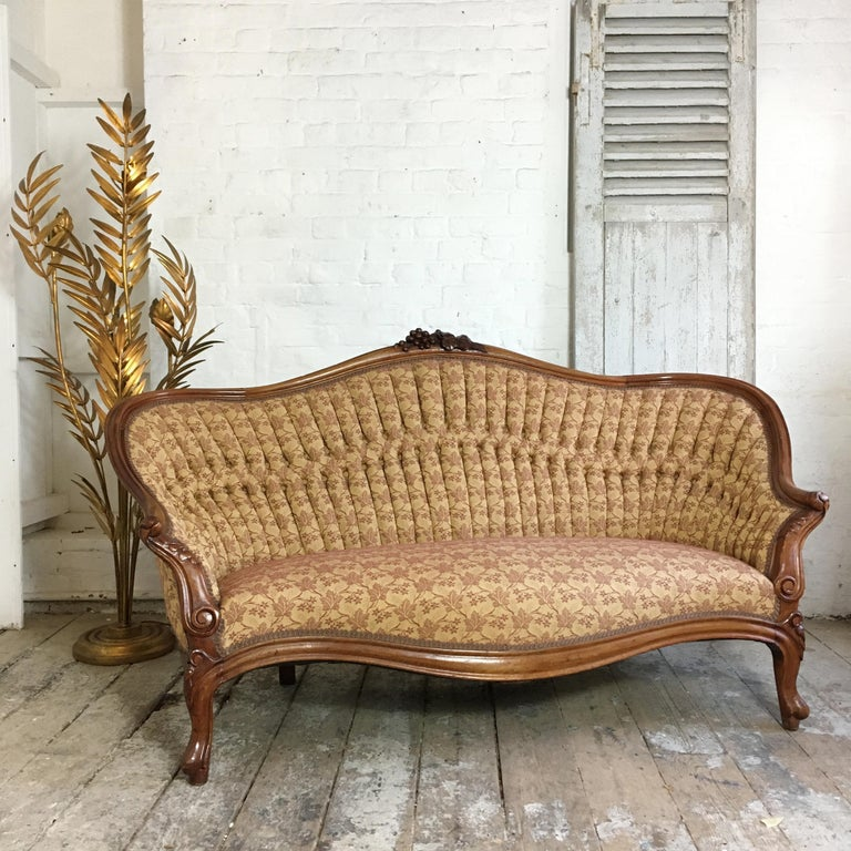 Antique French walnut settee, circa 1890s, cabriolet legs, double pleated buttoned back, upholstered in a soft gold beige jacquard with grape design woven through, this Grape design matches back to the carved grape and leaf crest on the top of the