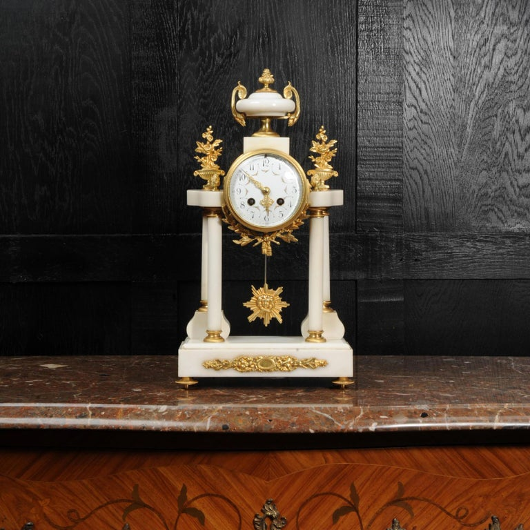 A beautiful original antique French portico clock, circa 1880. It is made of white marble mounted with ormolu (finely gilded bronze). The movement is held aloft on four marble pillars with the ormolu pendulum swinging gently below.  The dial is