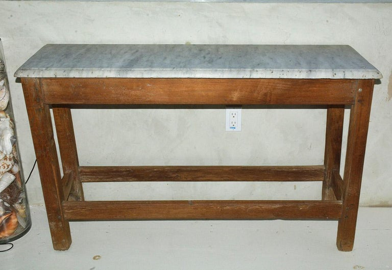 The wonderfully sturdy rustic French country Provincial style work table or serving console table is constructed of slotted framing to hold a veined marble top having beveled edges with wonderful aged patina and lots of character. Can be used as