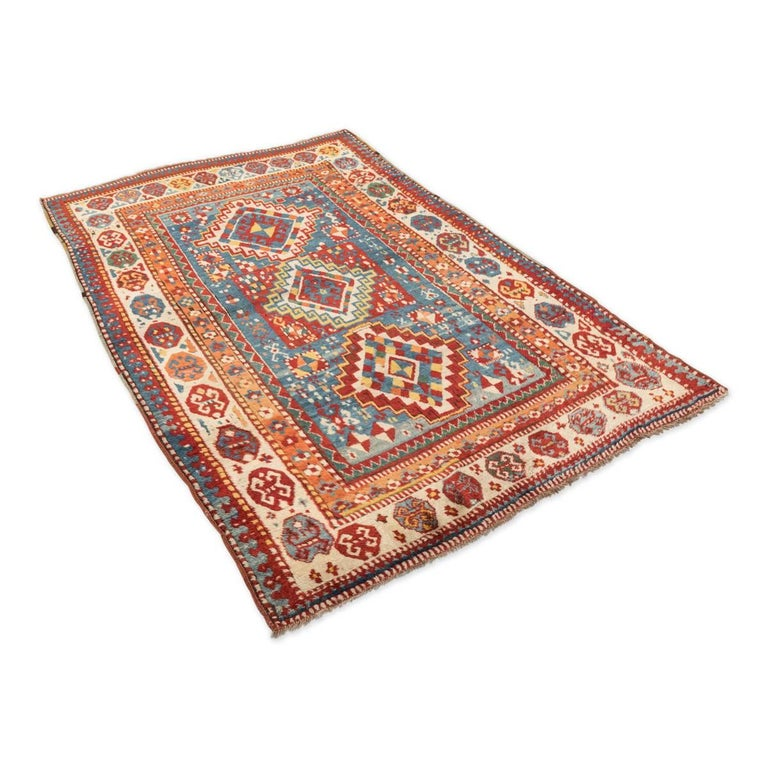 Rug of the Caucasus region of nomadic origin - Elaborated with a geometric design on an axis of three central diamonds that each one of them is different. - Use of very hard colors to find like turquoise blue and orange. The beige tone appears in