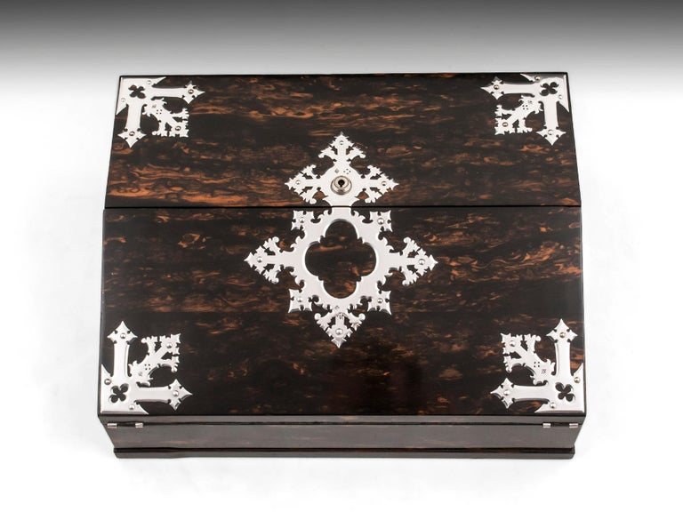 An unusual and rare design Writing Box by renowned cabinetmakers G.Betjemann & Sons, retailed by Toulmin & Gale, London. Veneered in beautiful figured exotic coromandel, complemented by a stunning satinwood interior. With ornate sterling silver