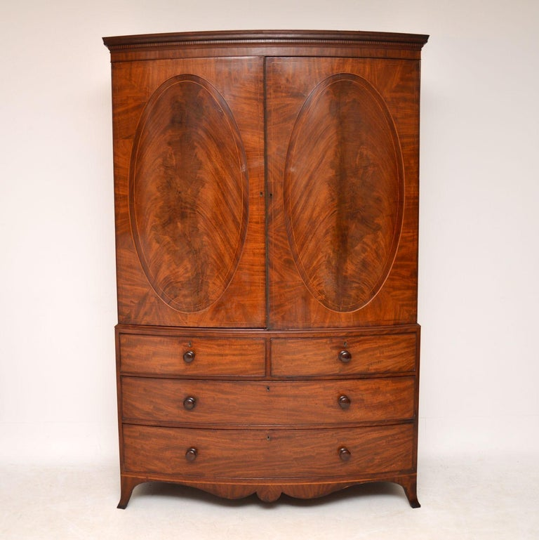 Very impressive antique George III mahogany Linen Press Dating from circa 1800 period and in very good condition. Its bow fronted, with oval flame mahogany panels on the top cupboards and it still has the original brass beading on the door. There