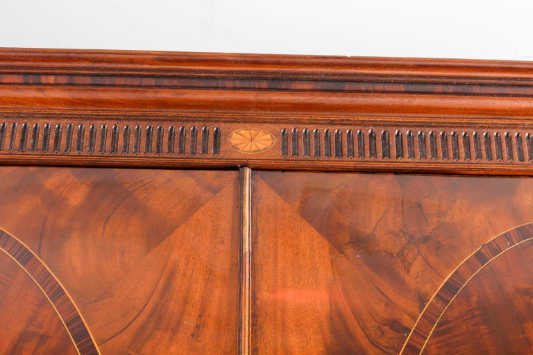 This is an impressive antique George III flame mahogany breakfront wardrobe compactum, circa 1780 in date.   The wardrobe has strong architectural lines and features an elegant moulded cornice above a fluted frieze decorated with inlaid satinwood