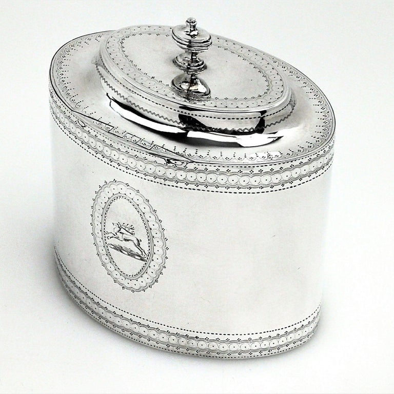 An antique George III Georgian silver tea caddy in a Classic Adams style straight sided oval form. This tea caddy is embellished with delicate bright cut engraved details. The caddy has pair of oval cartouches with an armorial in one and a crest in