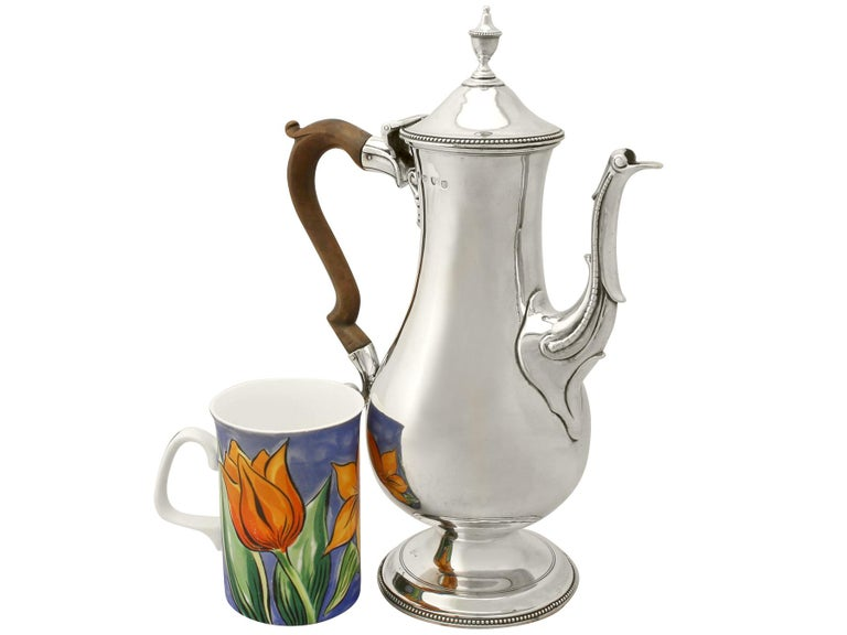 An exceptional, large and impressive antique Georgian English sterling silver coffee pot by Hester Bateman an addition to our silver teaware collection  This exceptional antique George III sterling silver coffee pot has a plain baluster shaped
