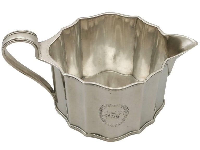 A fine and impressive, large antique George III English sterling silver cream jug made by Henry Chawner, an addition to our Georgian silver teaware collection  This fine antique George III sterling silver cream jug has an oval shaped form.  The