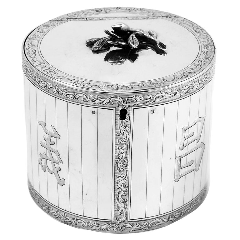 A beautiful Antique George III solidSilver Tea Caddy in a traditional circular straight sided can shaped form and is decorated with beautiful and detailed engravings. These engravings form ornate scroll borders which create panels on the side of