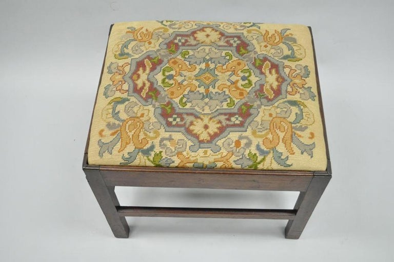 Antique George III English solid mahogany needlepoint bench. Item features solid mahogany stretcher supported base, square section legs, beautiful needlepoint upholstered seat, circa early 19th century. Measurements: 19