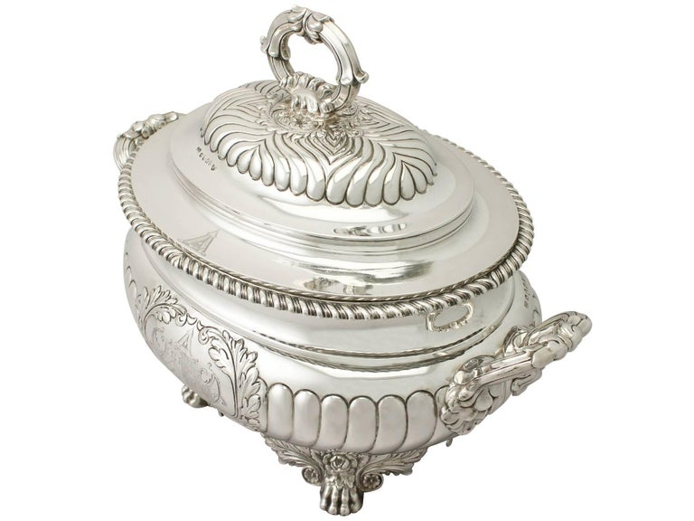 A magnificent, fine and impressive, rare antique George IV English sterling silver soup tureen assayed in York; an addition to our dining silverware collection.  This magnificent antique George IV English sterling silver soup tureen has an oval
