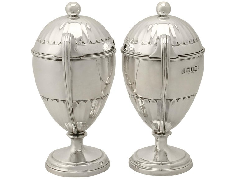 An exceptional, fine and impressive pair of antique George V English sterling silver preserve pots; an addition to our silver cruet and condiments collection.  These exceptional antique George V sterling silver preserve pots have a plain bell