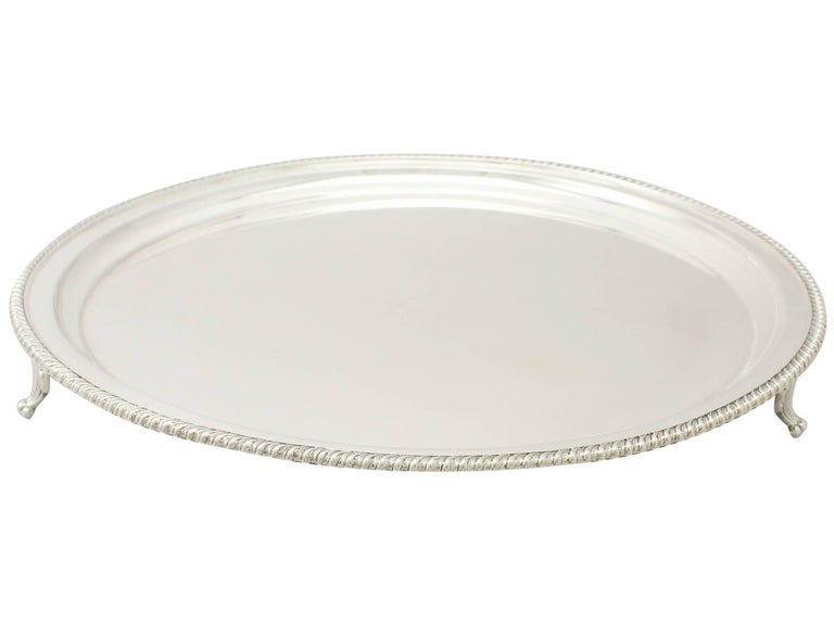A fine and impressive antique George VI English sterling silver salver; an addition to our range of silver trays and salvers.  This exceptional antique George VI sterling silver presentation salver has a plain circular form.  The surface of this