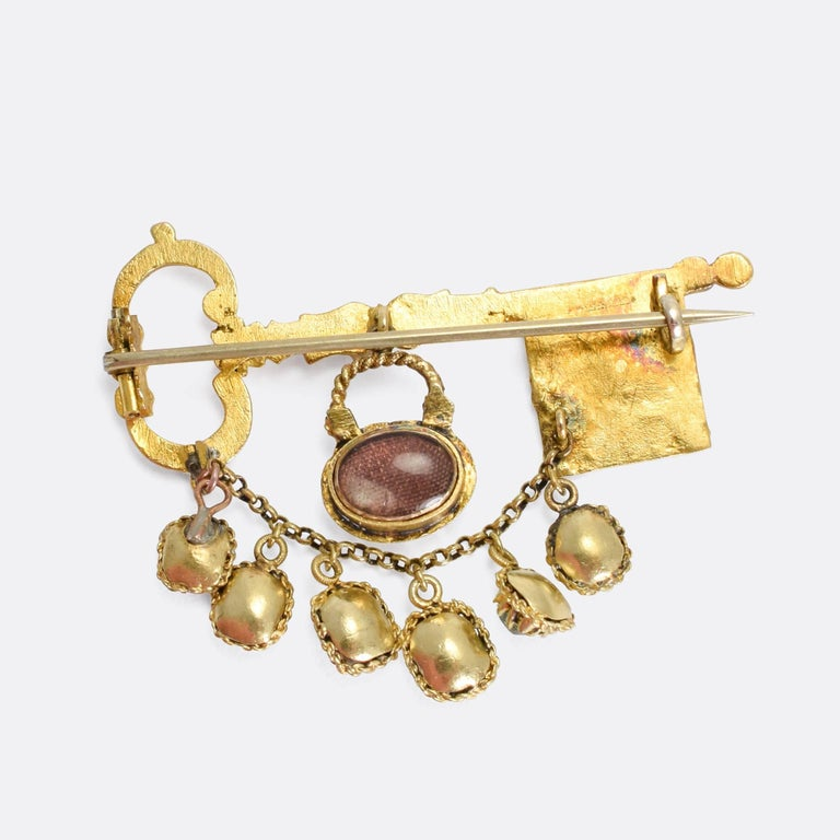 A spectacular, Museum quality, acrostic brooch dating from the early 19th Century. The main body is a beautifully hand-chased gold key, featuring intricate cross-hatched patterns and foliate details. Dangling from the key are two further components: