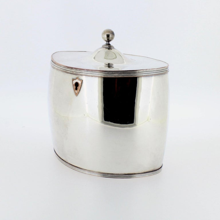 A fine, period Sheffield Plate tea caddy.  With simple streamlined lines of the early 19th century, a shield cartouche, and a ball finial.  Simply a wonderful antique Georgian tea caddy that perfectly dovetails with modern taste!  Width: ca. 5 1/4