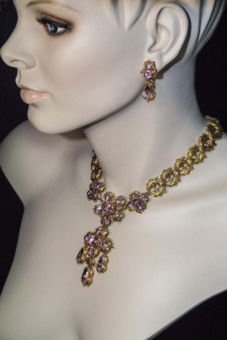 Circa 1830  This ornate antique pink topaz and 14K gold set is comprised of a superb quality necklace and a pair of earrings. The pendant can be detached and worn as a brooch.  Total length of the necklace 42 cm (16 3/4 in.)  Weight:  65