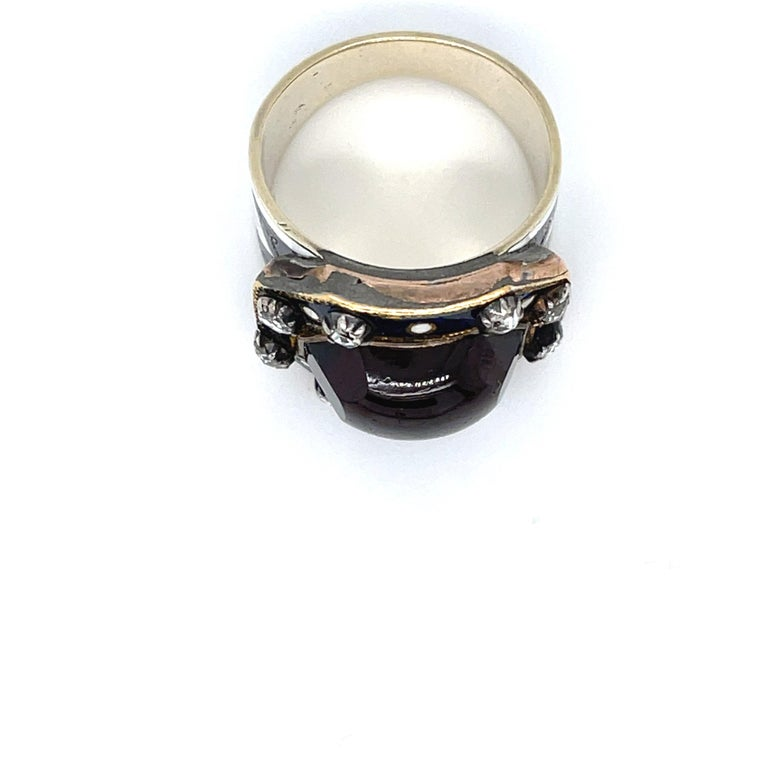 Antique 18k yellow gold Georgian ring centering on a large garnet surrounded by enamel and rosecut diamonds, circa 1820. The large garnet has minimal facets, but it is domed in shape. The ring has blue and white enamel with gold cross accents.
